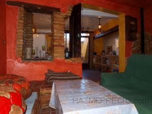 En la cocina hemos utilizado como decoración ladrillo rustico, madera maciza, piedra natural y en esta parte también hay una chimenea y un banco de obra con ladrillo rustico y cerámica rustica