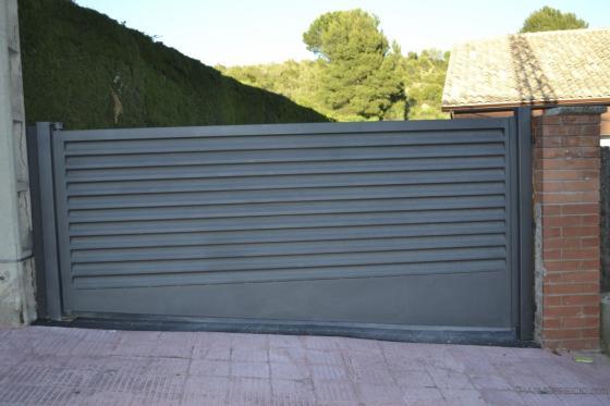 Puerta batiente motorizada con lama veneciana en forja.