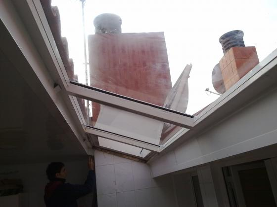 techo de cristal fijo transparente con claraboya abatible para poder limpiar los cristales.