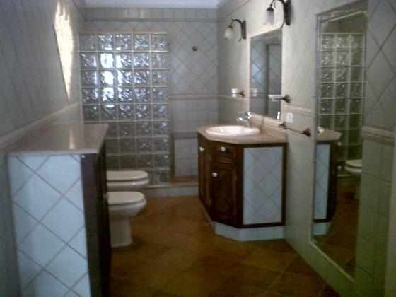 Realización de baño con plato ducha y muebles hechos de fábrica in situ.