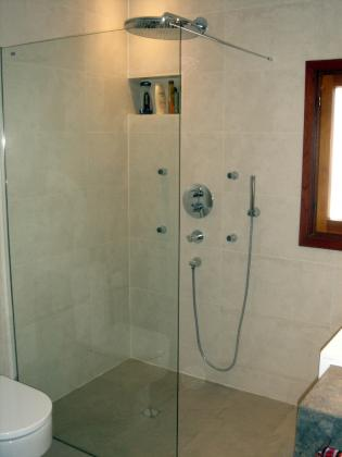 ducha rehalizada de obra , con la misma baldosa del suelo. grifería termostatica empotrada