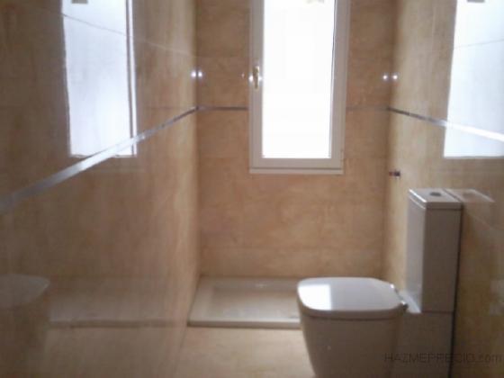 Alicatado con azulejo porcelanico en baño.