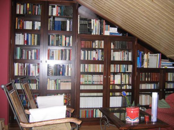 Mueble en ángulo. Librería en bajocubierta o buhardilla. Revestimiento de techo en madera