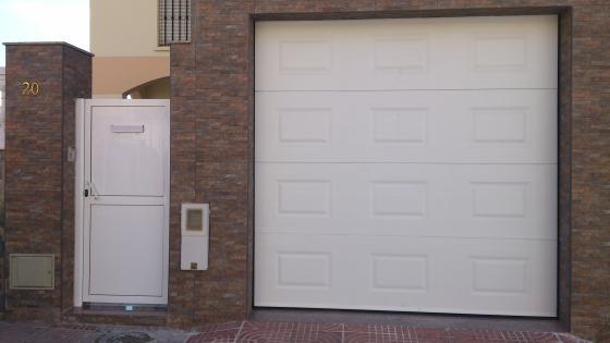 Conjunto de puerta de acceso peatonal y puerta seccional panel tipo cuarteron.