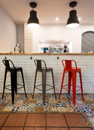 """En la barra de cafetería, cuyo frontal forramos con nuestro panel de ladrillo macizo color blanco, colocamos unos taburetes metálicos de colores que junto con las lámparas en negro ayudan a crear un ambiente """"industrial"""" que es última tendencia."""