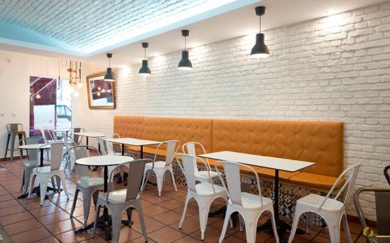 Las sillas y taburetes estilo Tolix escogidos para el proyecto tienen su origen el la Francia del siglo pasado, y consiguen recrear el ambiente tradicional de pastelería parisina que habíamos buscado. El banco corrido color mostaza aporta calidez y elegancia al ambiente.