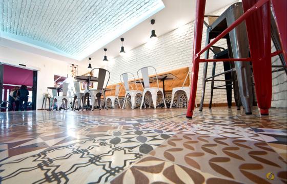 """El suelo se conservó en su mayor parte el original, pero se """"actualizó"""" con la instalación de algunas zonas con suelo cerámico que imita la baldosa hidráulica. La cenefa de suelo nuevo ayuda a delimitar la zona de expositor y barra de cafetería."""