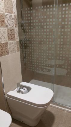 Alicatado con azulejo y solado con pavimento gres porcelanico, con plato de ducha de carga mineral y mamapara de vidrio templado.