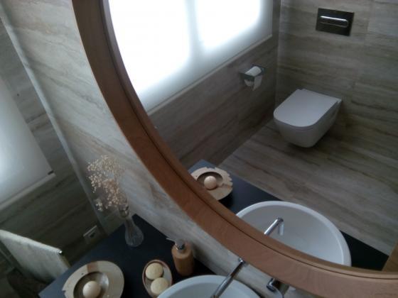 Detalle del remate en madera natural del espejo de este pequeño baño de diseño, donde se ve reflejado en Wc suspendido.