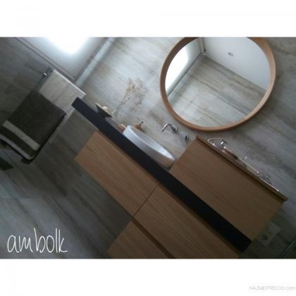 Mueble de baño a medida, suspendido, realizado en madera de roble en acabado natural con encimera teñida. A juego con espejo de diámetro 900mm con moldura en madera de roble natural con remate en ochava.