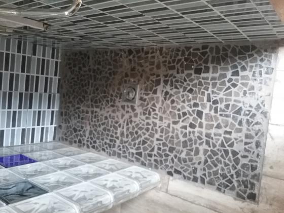 Plato de ducha de obra a la altura del suelo, echo con gres te de piedra gris