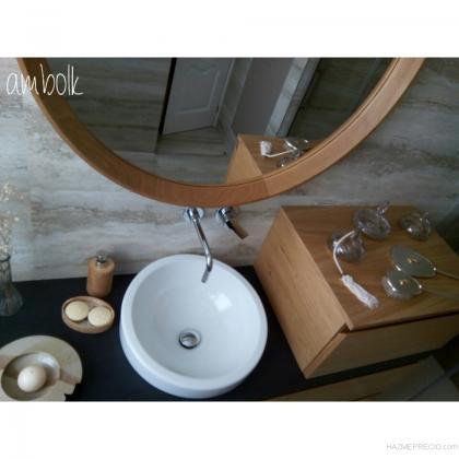 Detalle de la encimera de baño en roble teñido, con lavabo sobreencimera y grifería empotrada en la pared.