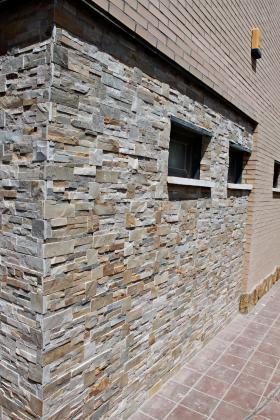 Picado de monocapa en fachada y posteriormente chapado con lajas de piedra natural