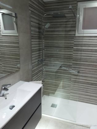 Mueble de baño color oscuro con lavabo de porcelana blanco, luces led inferiores, mueble suspendido