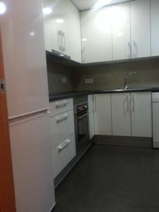 acabada cocina suelo de color negro pared de color gris armarios blanco brillantes