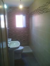 La elección de colores para alicatado de paredes y suele en tonos beige y tabaco, combinando azulejos lisos con azulejos de mosaico para dar dinamismo al baño- Organización de sanitarios en una única pared facilitando la movilidad espacial en el baño.