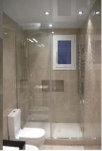 Colocación de una mampara transparente más toallero.  Colocación de una ventana de aluminio.