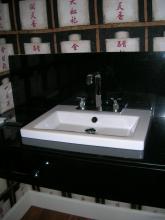 lavabo aseo de invitados, encimera de granito negro, lavabo duravit, desagüe visto cromado, paredes enteladas.