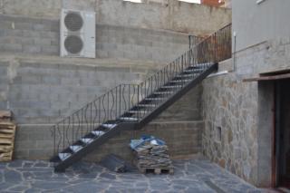 Vista lateral de la escalera exterior. Todos los barrotes han sido modelados  mediante el método tradicional de la forja. Trabajo acabado en oxirón negro pavonado