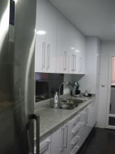 Bancada con muebles altos y bajos, alicatado con azulejo blanco y negro brillo, encimera de granito