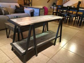 Mueble hecho con tubo cuadrado de hierro, simulando unos caballetes con dos tableros.