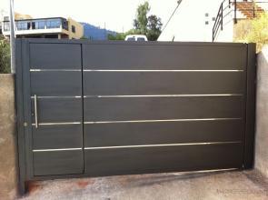Puerta batiente fabricada en hierro con detalles de acero inoxidable.