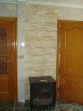 Vista de la pared trasera aplcada con piedra natural, y la chimenea colocada.