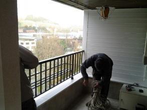 Debido a las dimensiones de la ventana (2600mm x 1700 mm) no se podía subir por la escalera del portal y hubo que subirla por la fachada con cuerdas. En la foto se puede apreciar a los montadores preparando las cuerdas.