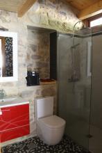 Sobre el muro de piedra de la vivienda se suspende el mobiliario del baño a modo de accesorio, sin quitarle el protagonismo a la piedra vista.