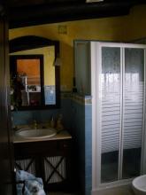 Cuarto de baño rustico completo alicatado a media altura.