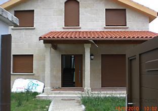 Entrada a la vivienda unifamiliar, donde se ve la fachada principal con el porche cubierto que da acceso tambien desde la cocina para poder desayunar o comer en el porche.