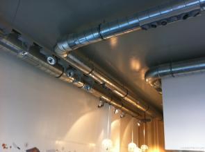Sistema de climatizacion con tubo de chapa visto con salidas de aire con toberas de largo alcance. Sistema de renovacion del aire con tubo de chapa visto con extraccion del aire mediante rejillas.