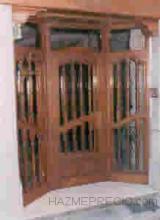 Puerta en madera de Bubinga con laterales fijos y tarje superior, cierre de postigo interior acristalado.
